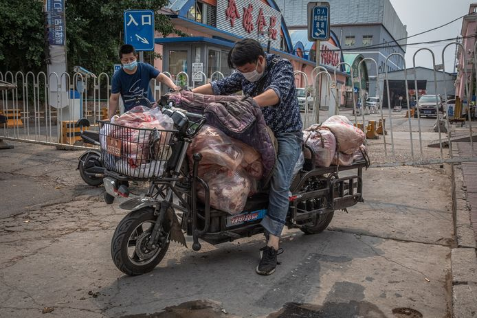 Een man met een scooter vol vlees verlaat  de gesloten Xinfadi markt.