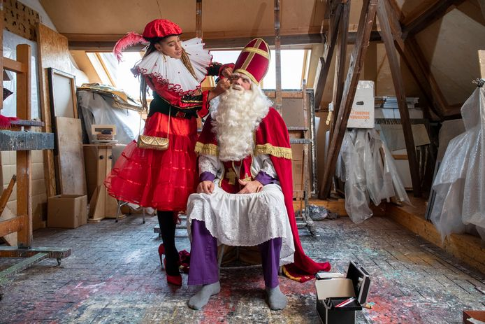Hoofdpiet Onyema Onwuka helpt Sinterklaas Martijn Adelmund bij het aankleden.