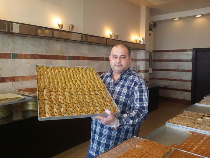 De Libanese bakker Ibrahim el Yamani toont zoet gebak dat hij maakt in zijn bedrijf in Saida.