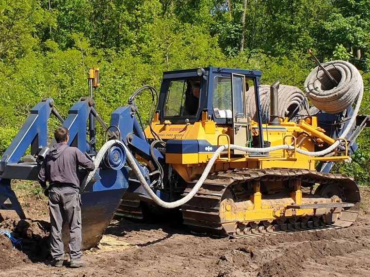 De aanleg van draineerbuizen in het land. Beeld