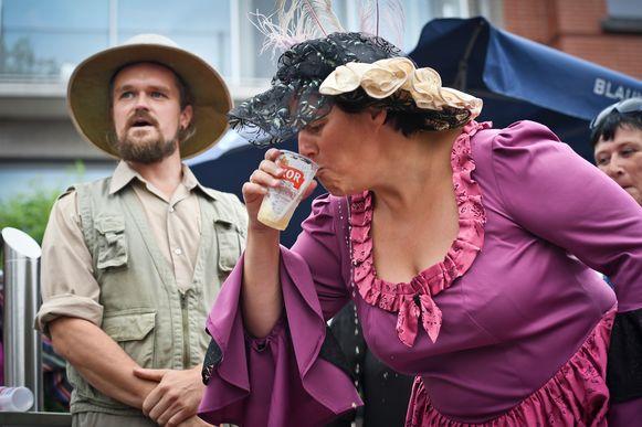 Een dame houdt het pintje op een veilige afstand van haar mooie jurk.