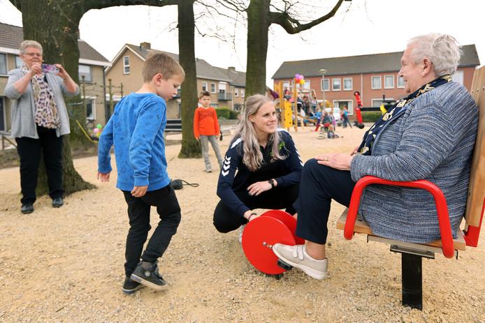Buurtsportcoach Demy Weertman (m) helpt buurtbewoonster Jeanne de Bruin (86) even op weg met de 'fiets'.