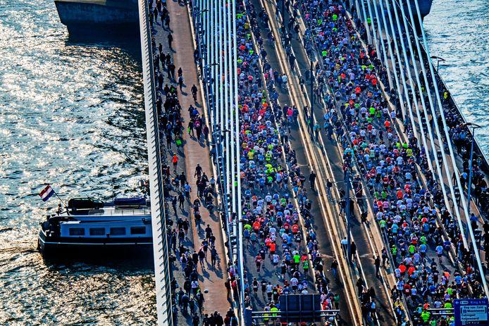 Lopers rennen over de Erasmusbrug na de start van de 39ste editie van de marathon.