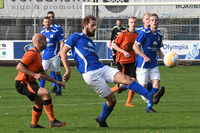 Archiefbeeld: Douwe Zwaan van Olympia'18 neemt de bal aan, Excellent-verdediger Stephan Schellekens kijkt toe.