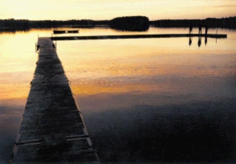 De ondergaande septemberzon weerspiegelt in het meer. (Trouw) Beeld