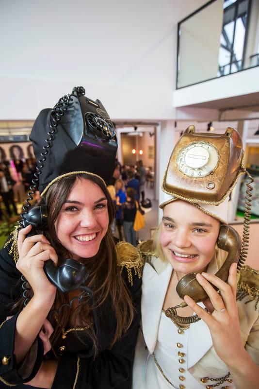 Twee gastvrouwen met telefoonuitdossing wachtten gisteravond de eerste gasten op bij de officiële opening.