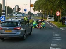 Scooterrijder klapt op busje, weg dicht
