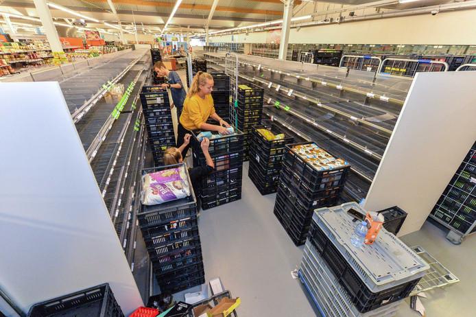 Personeel van AH haalt met met man en macht schappen leeg voor de verhuizing vanuit de tijdelijke winkel naar de nieuwe supermarkt in winkelcentrum Anklaar in Apeldoorn.