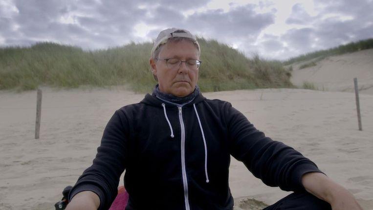 Nico Meijering mediteert op het strand. Beeld
