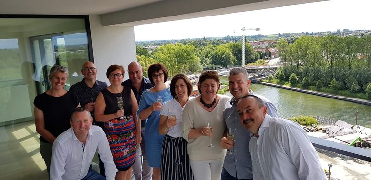 Een foto met links burgemeester Kurt Windels en schepen Trui Lambrecht met de acht gasten in de Valora-toren.