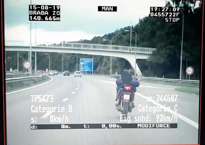 De bestuurder van de bromfiets reed zonder helm op de snelweg.