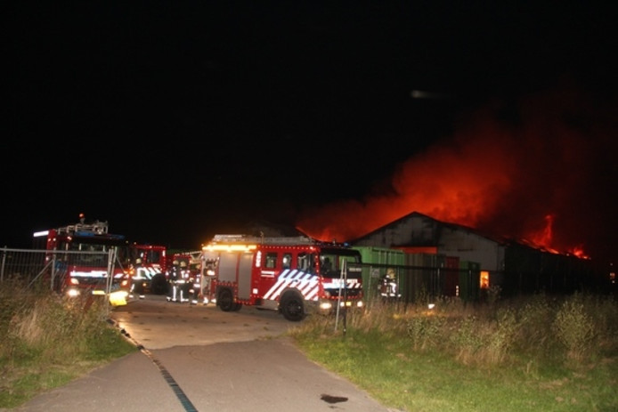 De brandweer laat de loodsen gecontroleerd uitbranden.