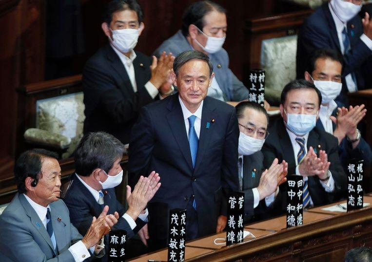 Suga (staand) woensdagochtend na zijn benoeming in Tokio. Beeld EPA