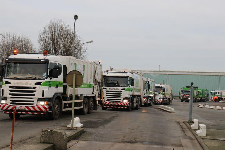Huisvuilwagens staan in lange rij te wachten aan de uitrit, maar kunnen niet vertrekken door een blokkade van de stakers.