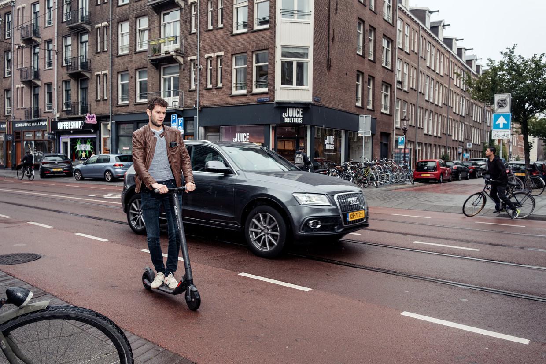Op het fietspad van de Van Woustraat zoeft de e-step soepel mee in het verkeer.