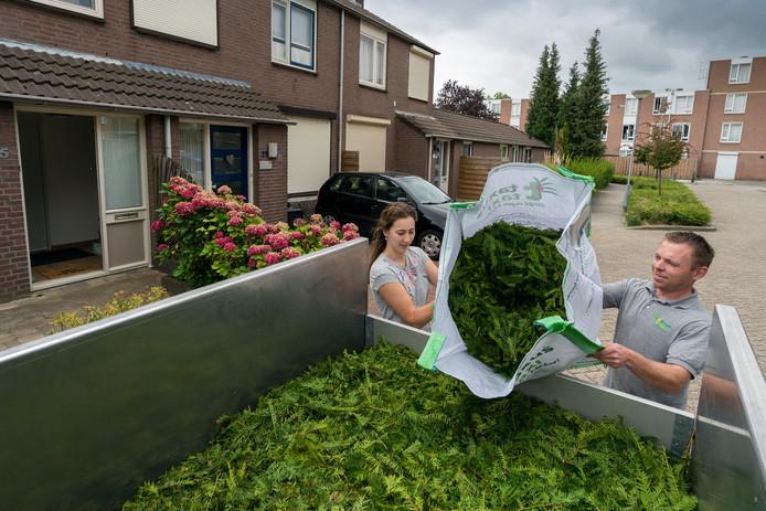 Nicole van den Elsen helpt Werner Toonen van de Taxus Taxi met de speciale zak te legen in de laadwagen.