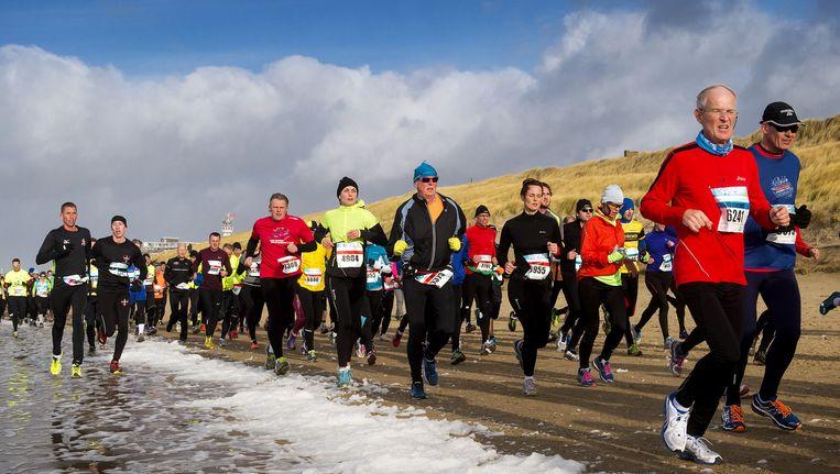 Marathondeelnemers lopen over het strand in Egmond aan Zee. Beeld anp