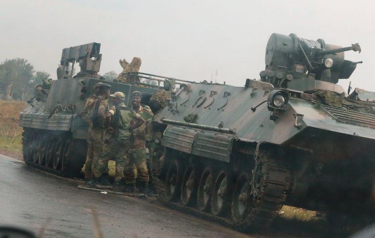 Soldaten staat bij militaire voertuigen even buiten hoofdstad Harare.