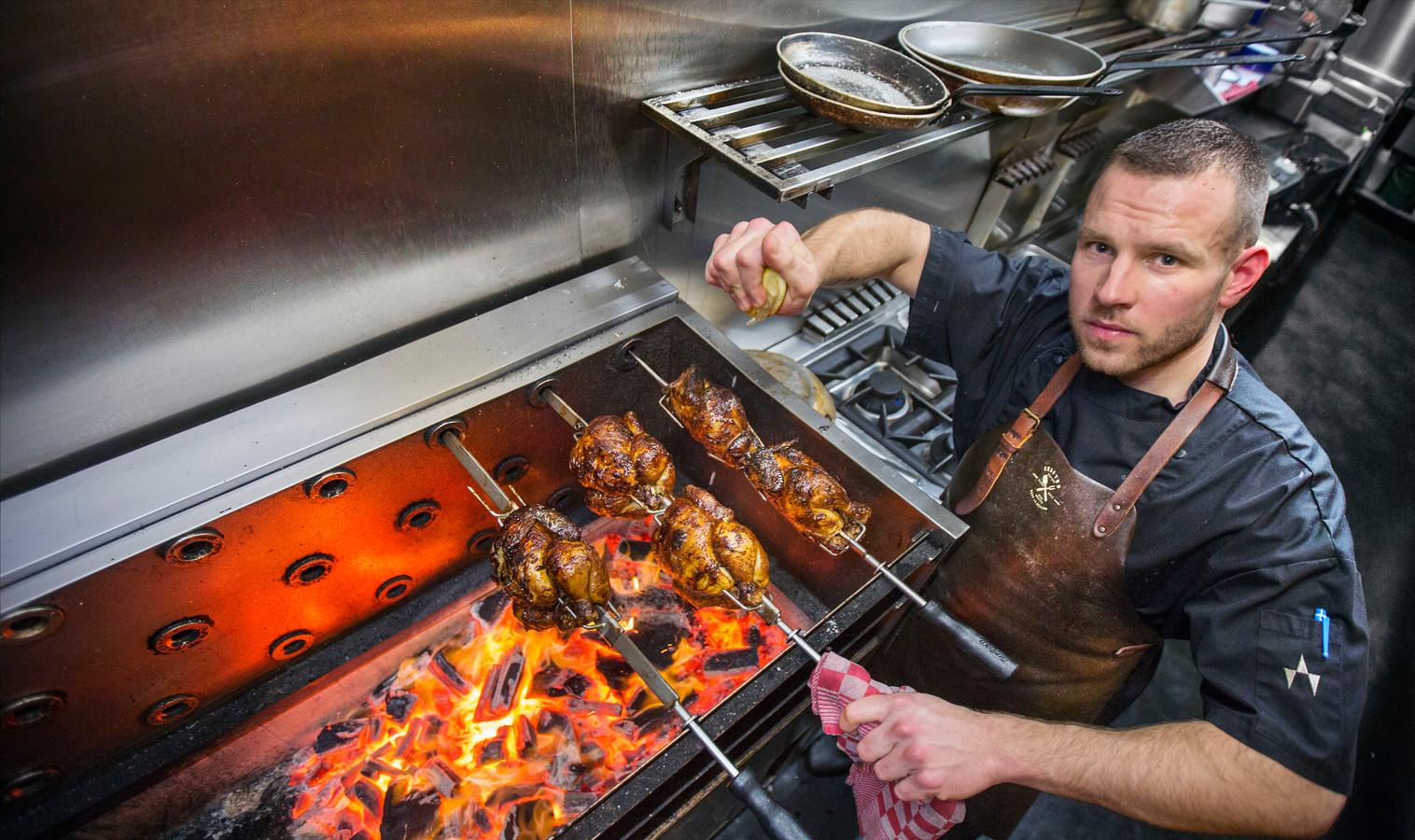 Chef Dave Becic sprenkelt verse citroensap op de gemarineerde kip.