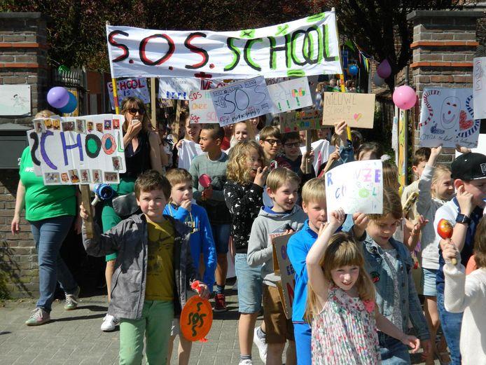 Met spandoeken, toeters en bellen, trekken de 120 leerlingen en hun ouders de straat op.