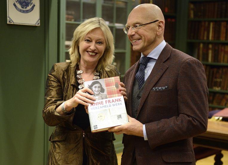 Uitgever Mai Spijkers (R) overhandigt het boek Verzameld Werk van Anne Frank aan minister Jet Bussemaker. Beeld ANP