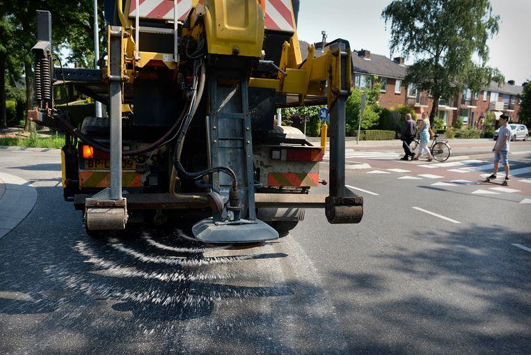 In juli 2015 rukte de gemeente Ede uit om het asfalt te beschermen. Beeld Marcel van den Bergh