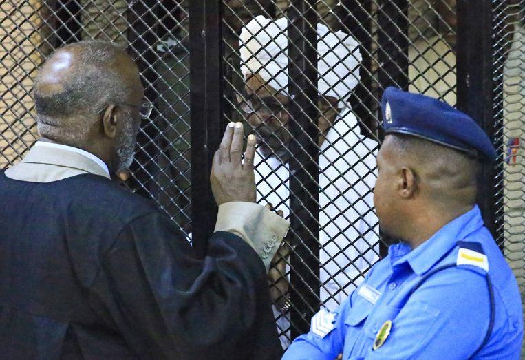 Voormalig president Omar al-Bashir van Soedan, die in april dit jaar door het leger werd afgezet, overlegt met een van zijn advocaten tijdens het proces tegen hem wegens corruptie. Hij werd zaterdag tot twee jaar veroordeeld. Beeld AFP
