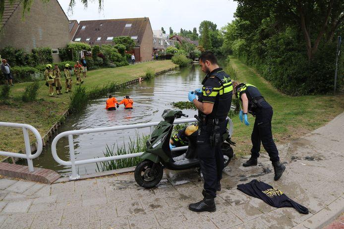 Terwijl de politie de gevonden scooter onderzoekt, speuren brandweermannen het water af