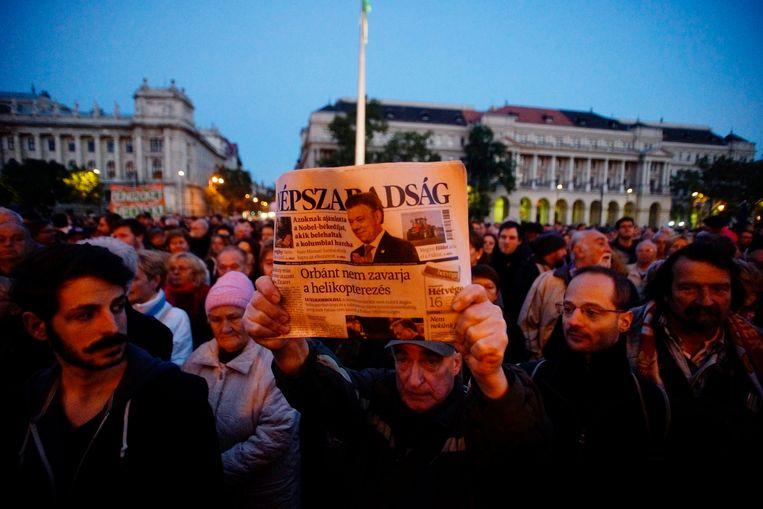 Een man toont begin oktober de laatste printeditie van de Hongaarse krant Népszabadság gedurende een demonstratie in Boedapest uit solidariteit met het politieke dagblad. Eerder die dag stopte de uitgever met publicatie van de krant, volgens de organisatie tijdelijk om een nieuw businessmodel te vinden. De krant werd uiteindelijk opgedoekt. Beeld EPA
