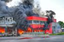 De vlammen bereiken ook het voorste gedeelte van het bedrijfspand.