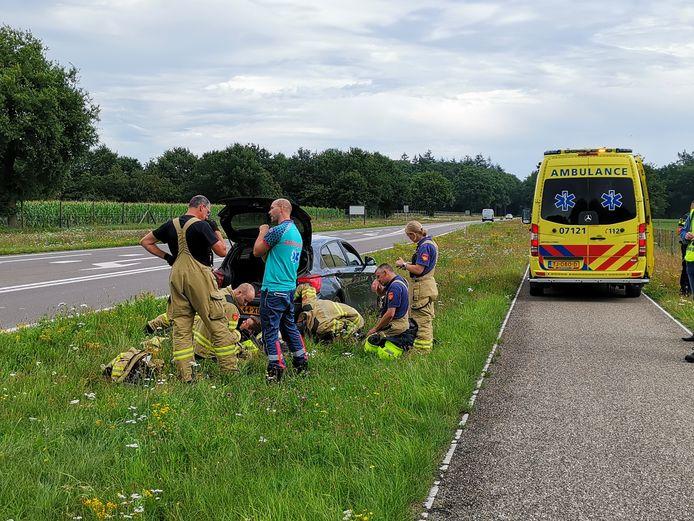Op de Verlengde Arnhemseweg in Ede botsten twee auto's tegen elkaar. De brandweer probeert een van de voertuigen te repareren.