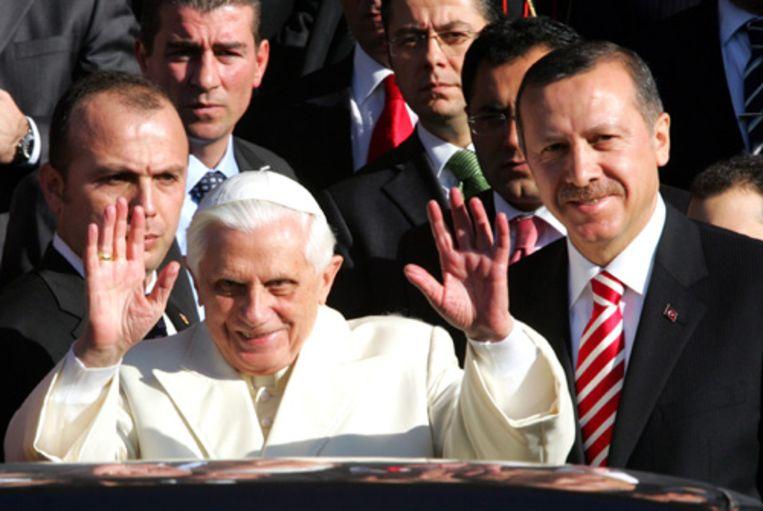 Paus Benedictus XVI wordt op de luchthaven van Ankara verwelkomd door premier Erdogan van Turkije. De persoonlijke ontvangst is een ongewone breuk met het protocol en een belangrijk diplomatiek gebaar van de Turkse premier, die kort voor aankomst van de katholieke leider nog zei dat hij de paus niet kon ontvangen. (AP) Beeld