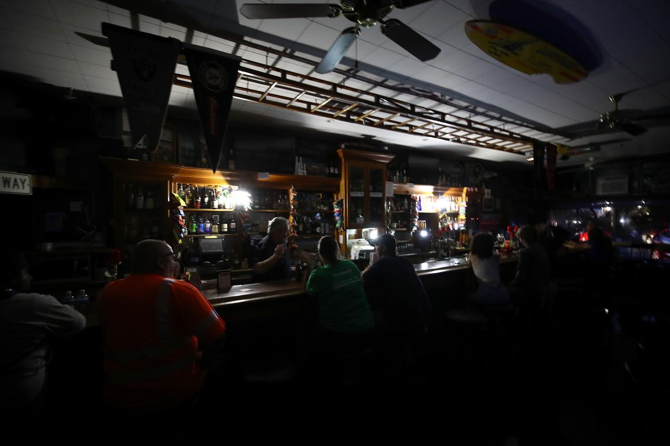 Dit café opende toch de deuren, hoewel klanten er in het donker zitten.