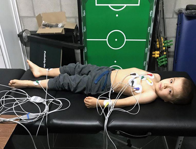 Een voetballertje hangt vol klevers en draden tijdens het onderzoek.