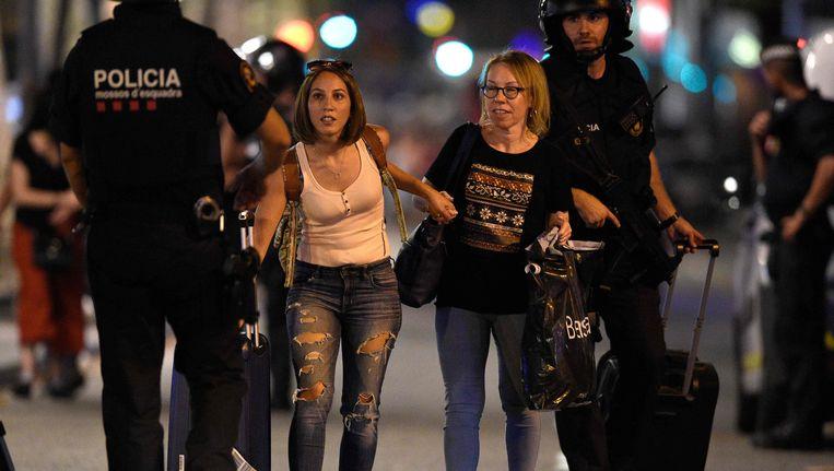 De politie leidt omstanders weg van de plaats waar donderdag in Barcelona een aanslag werd gepleegd. Beeld afp