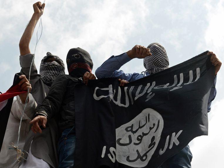 Jihadisten van de Islamitische Staat wapperen met een vlag. Beeld AFP