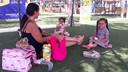 Een Spaanse mevrouw ontspant met haar dochters in het parkje.