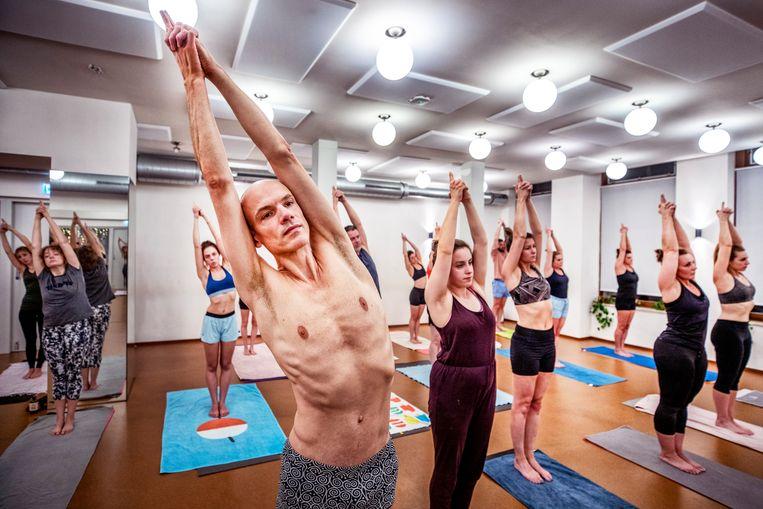 Bas Dorlandt (vooraan) geeft yogales in zijn school Bikram Yoga Den Bosch. Beeld Raymond Rutting / de Volkskrant