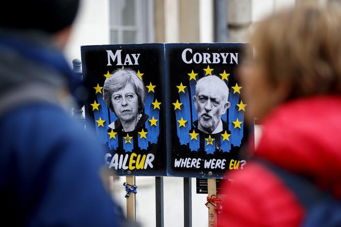 Posters met daarop Theresa May (links) en Jeremy Corbyn.