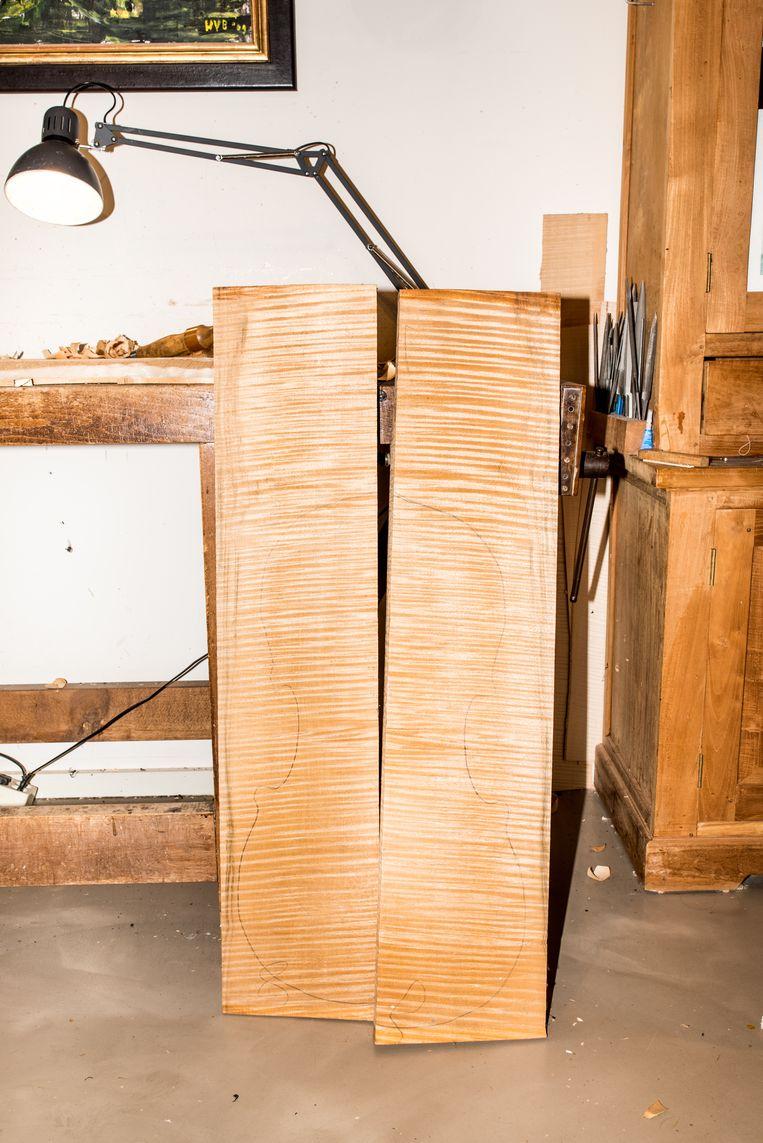 Contouren van een cello geschetst op twee planken, die aan elkaar gelijmd de basis vormen van een achterblad. Beeld Jan Mulders