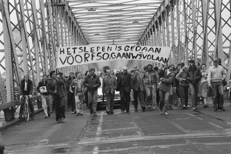 """Stakers trekken op 20 september 1979 in optocht over de Willemsbrug met een spandoek: """"Het slepen is gedaan, voor F 50,- gaan wij vol aan"""""""