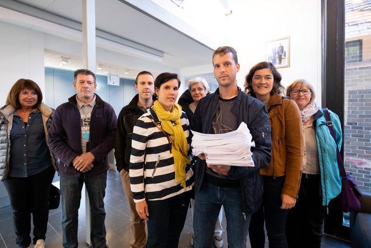 Het buurtcomité 'Houd Hingene uit de Wind' in het gemeentehuis met haar petitie.