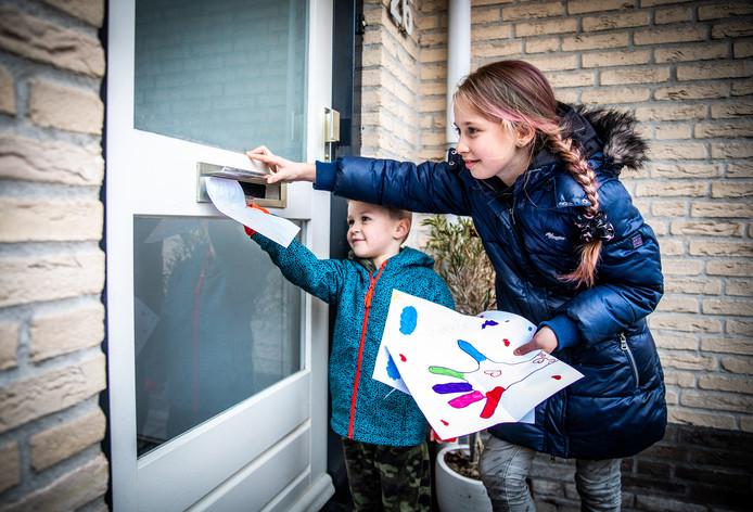 Daan en Tess brengen hun tekeningen rond in hun buurt in Maasdam.