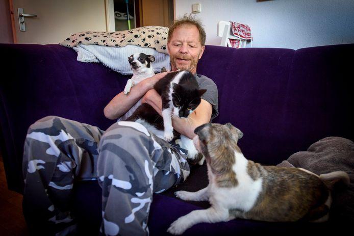 John Engels, thuis op de bank met enkele van zijn huisdieren.