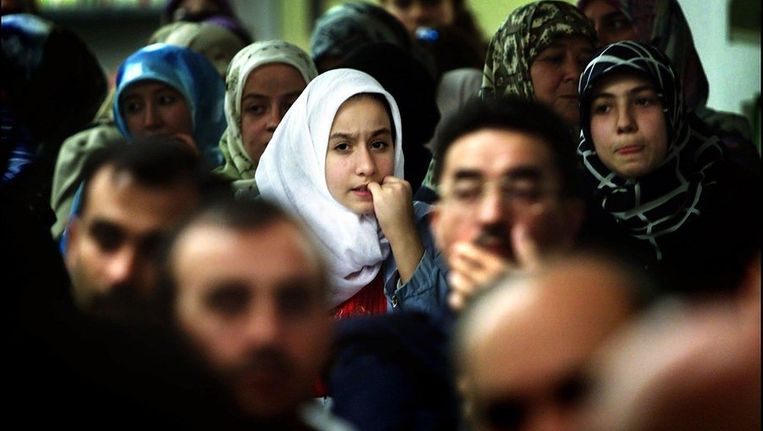 Een jonge vrouw bijt op haar nagels tijdens een van de toespraken van uniersiteitsbestuurders bij de opening van het nieuwe academische jaar van de Islamitische Universiteit in Rotterdam. Beeld ANP