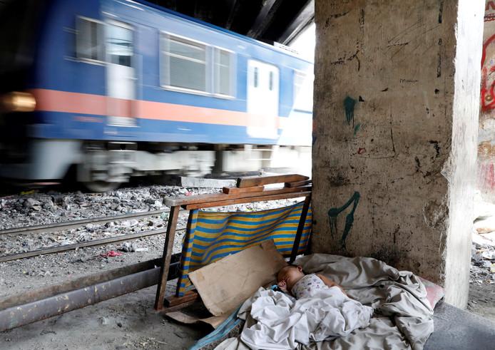 In het Filipijnse Manilla slaapt een baby in een provisorisch bedje naast de spoorrails. Foto Dondi Tawatao