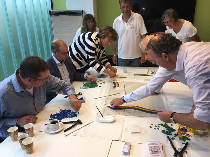 Burgemeester Wobine Buijs (gestreept vest) en vier wethouders werken aan een mozaïekregenboog. Organisatoren Alex van der Heijden en Elsbeth Fokker kijken in witte festivalpolo's toe.