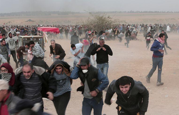 Palestijnse betogers rennen voor traangas tijdens confrontaties met Israëlische soldaten langs de grens tussen Gaza en Israël.