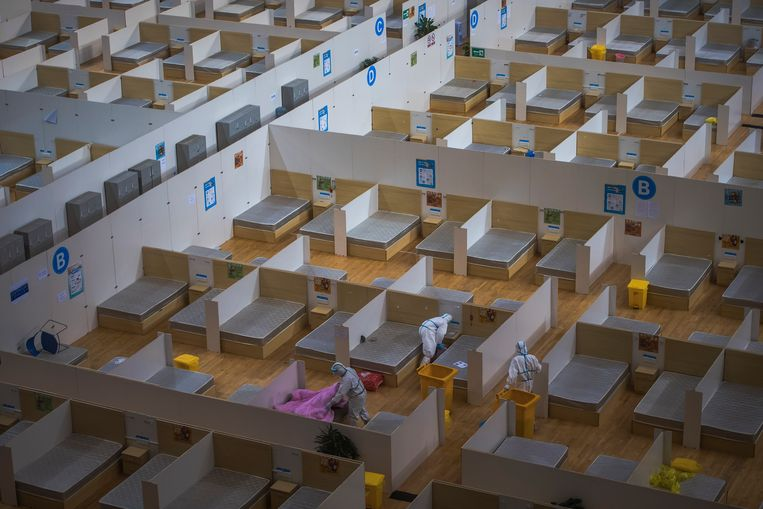 Schoonmakers ruimen een sporthal leeg die in Wuhan dienst deed als ziekenhuis.    Beeld AP
