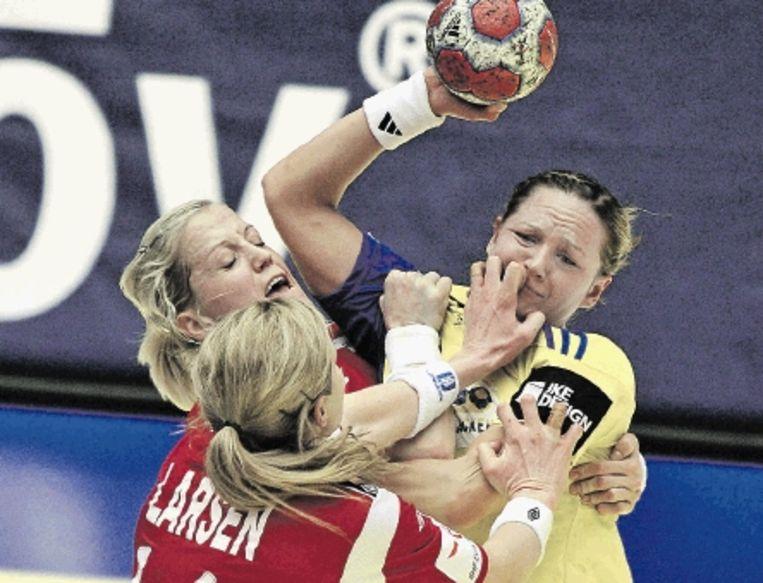 De Zweedse Helgeson (rechts) wordt door de Noorse speelsters Larsen en Loke in de mangel genomen. In de Scandinavische finale van het EK handbal ging de overwinning naar de Noren: 25-20. ( FOTO AFP) Beeld AFP
